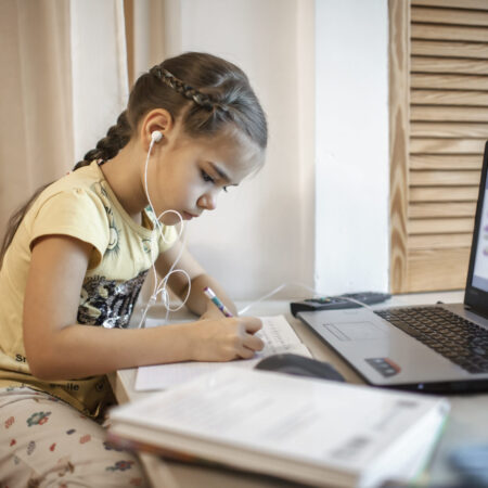 Distant education, online class meeting. Pretty schoolgirl in formal shirt but in pajama trousers studying during online lesson at home, social distance during quarantine, self-isolation