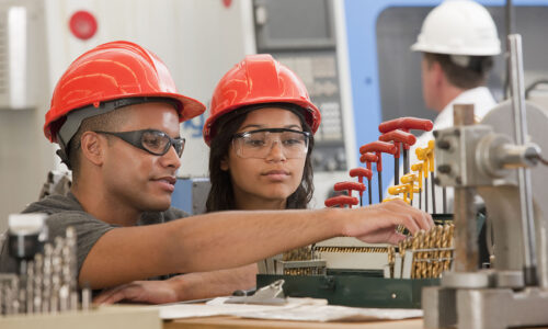 Engineering students selecting drill bits for a CNC machine